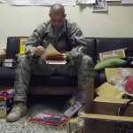 Kaluza reading letters from SO4LS with dog toys and care packages